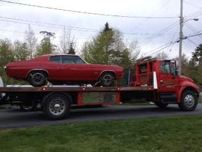 red car on flatbed tow truck