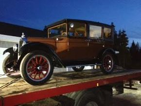 Antique car on flatbed tow truck