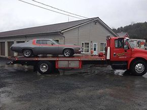 silver car on flatbed tow truck