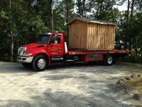 Shed on a flatbed tow truck
